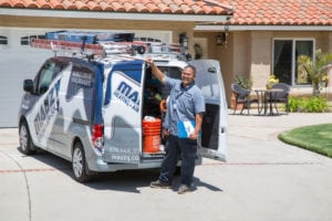 mauzy technician standing beside service van for furnace installation san diego ca