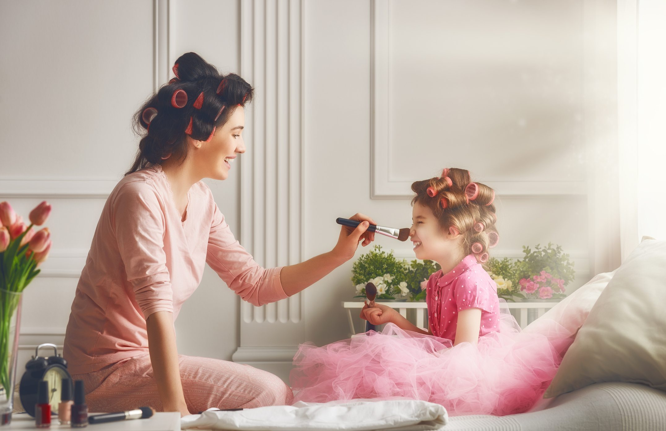mom playing dress up with daughter inside their home