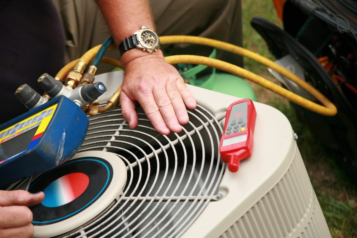 technician maintaining air conditioning unit with tools