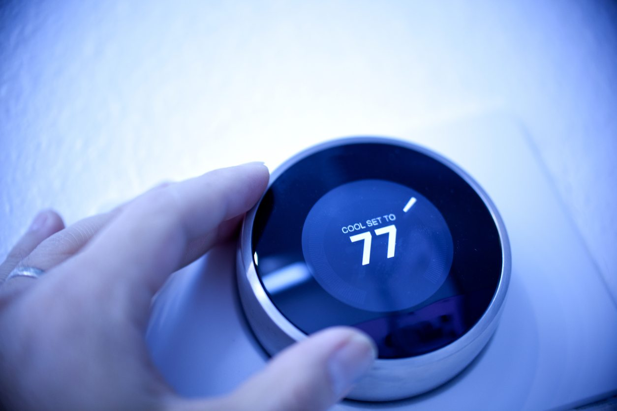 man controlling temperature on a nest thermostat