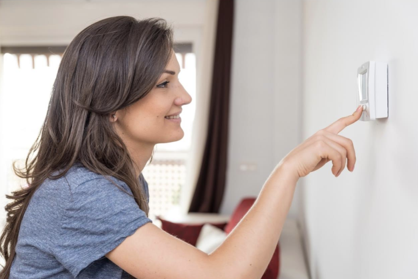 A resident in San Diego adjusts her thermostat when returning from work to effectively manage her energy usage and keep energy bills low.