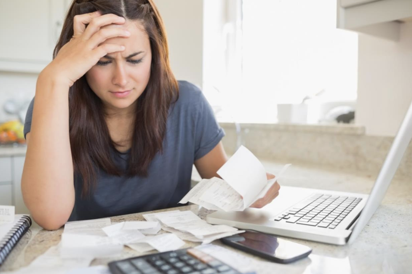 Homeowner reviewing bills trying to save money on her energy bill.